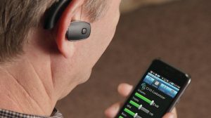 picture of man tuning bluetooth hearing aid with cell phone
